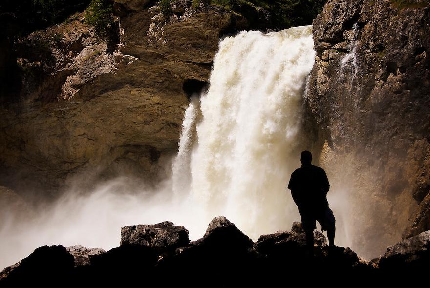 A hiker stands before Natural Bridge Falls near McLeod, Montana.