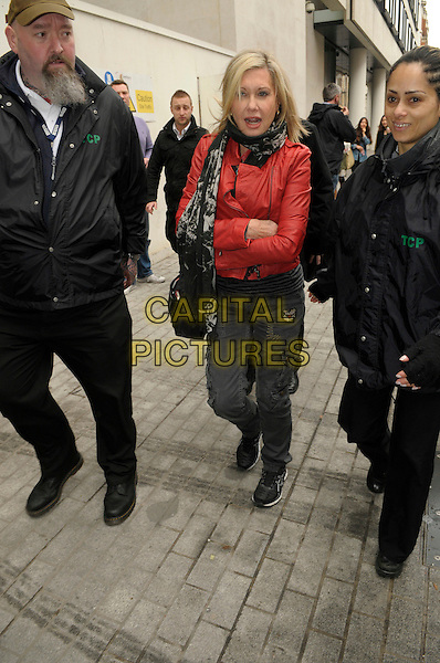 Olivia Newton John.Leaving BBC Radio 2 London, England. 18th April 2012.full length black trousers red leather jacket arms crossed bag purse scarf minder security bodyguard.CAP/IA.©Ian Allis/Capital Pictures.