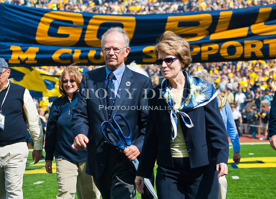 Former Athletic Director Bill Martin, center, and University President Mary Sue Coleman, right, walk off the field after a ribbon-cutting ceremony to re-dedicate Michigan Stadium, before an NCAA college football game, Saturday, Sept. 4, 2010, in Ann Arbor, Mich. After a three year, $226 Million renovation, the Big House is now bigger than ever, reclaiming the country's title as largest college football stadium in capacity. (AP Photo/Tony Ding)