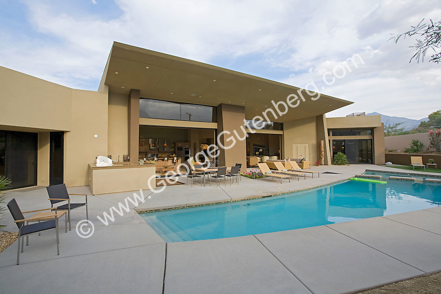 Curved Swimming pool in front of very modern home