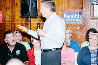 People listen as Republican presidential candidate and Ohio governor John Kasich speaks at a town hall campaign event at the Derry VFW in Derry, New Hampshire.