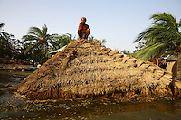 A man sits on the roof of his submerged home. Thousands of people were displaced in Shyamnagar Upazila, Satkhira district after Cyclone Aila struck Bangladesh on 25/05/2009, triggering tidal surges and floods..