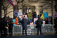 Baltimore City Police and Air Force guard the parade route in front of religious protesters ahead of the inauguration of Barack Obama as the 44th President of the United States. 42,500 police and security personnel watched over the crowd. The protest appeared to denounce Obama for his views on homosexuality, among other things.