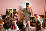 Education preschool 3-4 year olds male teacher doing counting activity with class holding up fingers numeracy horizontal