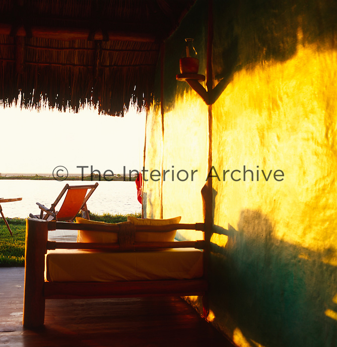 A daybed at the Hotelito Desconocido bathed in evening sunlight under the shade of the thatch with brightly coloured deckchairs in the garden beyond