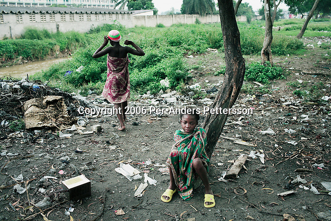 KINSHASA, DEMOCRATIC REPUBLIC OF CONGO - APRIL 30: Esther Yandakwa, age 9, dries her body after taking a bath in a river on April 30, 2006 in Matonge district in central Kinshasa, Congo, DRC. Esther is homeless and works as a prostitute with four fourteen-year-old friends. They live outside, next to a polluted river. She's been three years on the street and has run away from here family. She has from time to time been living in a homeless shelter for children, but doesn't like the rules there. She usually smokes cigarettes, marijuana, drinks whiskey and sometimes takes Valium. She charges the clients as little as US$ 1. About 15,000 children are estimated to live on the streets of Kinshasa. Congo, DRC is in ruins after forty years of mismanagement by the corrupt dictator and former president Mobuto Sese Seko. He fled the country in 1997 and a civil war started. The country is planning to hold general elections by July 2006, the first democratic elections in forty years.(Photo by Per-Anders Pettersson)