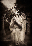 Statue of an female angel praying in Brompton Cemetery, London