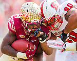 Florida State running back Dalvin Cook takes a vicious hit from NC State defensive end Mike Rose during their NCAA homecoming game against NC State in Tallahassee, FL November 14, 2015.  Florida State defeated N.C. State 34-17.
