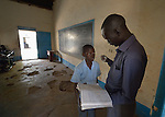 A teacher reviews a student's work at the John Paul II School in Wau, South Sudan.