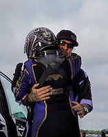 Aug 31, 2014; Clermont, IN, USA; NHRA funny car driver Alexis DeJoria (left) hugs husband, television personality Jesse James during qualifying for the US Nationals at Lucas Oil Raceway. Mandatory Credit: Mark J. Rebilas-USA TODAY Sports