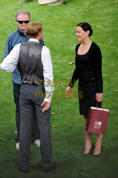 "JAMES D'ARCY & ABBIE CORNISH.on the set of Madonna's movie ""WE"" in London, England, UK, July 25th 2010. *Exclusive All-Rounder*.full length black top cardigan skirt bag grey gray waistcoat cast back rear behind on set location filmset film .CAP/IA.©Ian Allis/Capital Pictures."