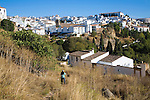 Man walking down path towards white buildings in newer area of Ronda, Spain