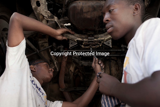 CAPE TOWN, SOUTH AFRICA - APRIL 20: Godfree Dlamini (L) , age 20, works on a car on April 20, 2012 in Cape Town, South Africa. She studies at a motor mechanics course who is dedicated to training five apprentices at a time, in motor car mechanics. The students come from poor backgrounds and have been unemployed until they cam here. iThemba Labantu offers these young men and women the opportunity to learn a trade so that they will be able to earn a living for themselves and their families one day. (Photo by Per-Anders Pettersson For Global Post)