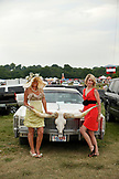 USA, Tennessee, Nashville, Iroquois Steeplechase, women in the infield pose in front of a Cadillac with horns