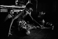 Siem Reap, Cambodia, December 2006..Hung Tiane Da, 38, is one of dozens of TB patients who live in very precarious conditions in insalubrious barracks at the back of the Provincial Hospital compound. His son Tiane Chai, 7, massages his back to try and soften his constant accute pain.
