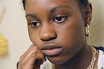 Teenage girl leaning on hand looking sad.  MR