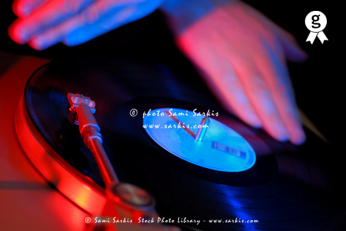 DJ spinning vinyl record on turntable, close-up (tilt, gel effect) (Licence this image exclusively with Getty: http://www.gettyimages.com/detail/73532515 )