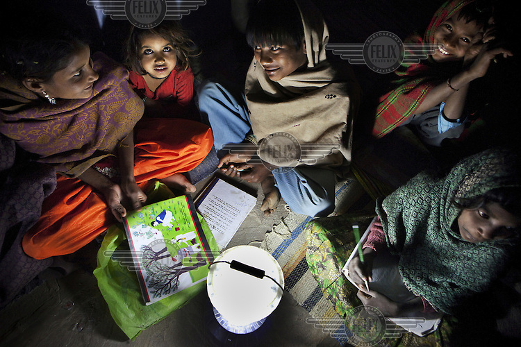 Poor children who work during day time go to school in the evening. Light is provided with solar light from the Barefoot College. The College aims to provide sustainable sources of alternative energy at the grassroots level.