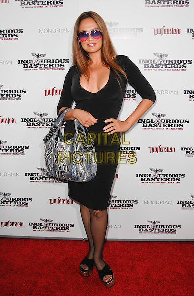"""TIA CARRERA .arriving at the Los Angeles premiere of """"Inglourious Basterds"""" at Grauman's Chinese Theatre in Hollywood, California, USA, August 10th 2009..full length black dress hand on hip bag silver snakeskin animal print sunglasses shades .CAP/ROT.©Lee Roth/Capital Pictures"""