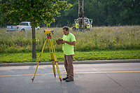 A surveyor marks elevation near where engineers collect soil core samples from lowland farm land near Alum Creek in Westerville, Ohio, where planners hope to build a multi-use development on farm land.
