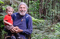 A local Caucasian man and a young part-Asian boy pause along the native forest loop trail at Kalopa State Park, Hamakua Coast, Big Island.