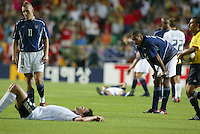 Clint Mathis and Tony Sannah catch their breath as exhausted German players lie nearby. The USA lost to Germany 1-0 in the Quarterfinals of the FIFA World Cup 2002 in South Korea on June 21, 2002.