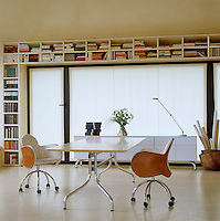 A pair of leather and linen saddle chairs by Vico Magistretti stand on either side of a worktable in a study with bookshelves built around the window