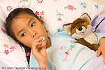 5 year old girl home sick in bed holding digital thermometer in mouth horizontal holding favorite stuffed animal fox Asian Vietnamese American horizontal