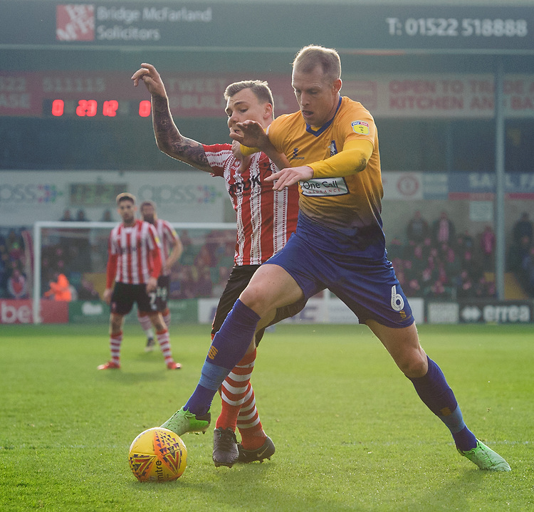 Lincoln City's Harry Anderson vies for possession with Mansfield Town's Neal Bishop<br /> <br /> Photographer Chris Vaughan/CameraSport<br /> <br /> The EFL Sky Bet League Two - Lincoln City v Mansfield Town - Saturday 24th November 2018 - Sincil Bank - Lincoln<br /> <br /> World Copyright © 2018 CameraSport. All rights reserved. 43 Linden Ave. Countesthorpe. Leicester. England. LE8 5PG - Tel: +44 (0) 116 277 4147 - admin@camerasport.com - www.camerasport.com