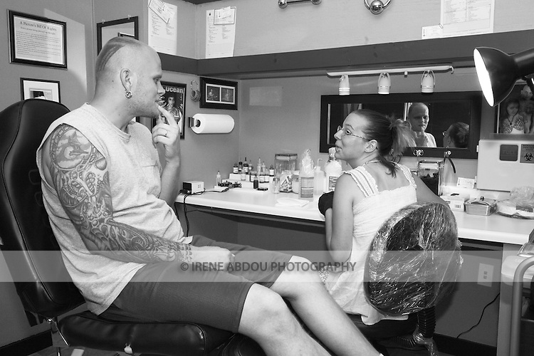 Tracy Baker, an apprentice piercer at a tattoo parlor in Rockland, Maine, listens to the instructions of her mentor on how to pierce his chin.