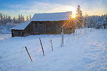Washington, Eastern, Spokane County. A barn and fence in a country landscape at sunset in winter.(lens flare)