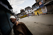An old man walks past the curfewed streets while soldiers from the paramilitary force, Central Reserve Police Force (CRPF) are seen patrolling the streets on empty streets in the downtown area of Nowhatta, Srinagar, summer capital of Jammu and Kashmir, India. A 50 hour curfew was imposed on May 5th to boycott the elections on May 7, 2009. ..Kashmir went into polls on the 4th round of Indian general elections. About 26 percent polling was recorded in the Indian parliamentary elections held in Kashmir on Thursday, May 7th 2009. The poll percentage was on the higher side this year as compared to 2004 polls when 15.04 percent polling was recorded.