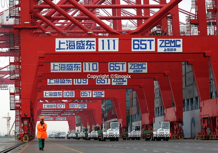 A dock worker standing beneath heavy dock cranes at the just completed Yangshan Deep Water Port in Shanghai, China. The port will give the city it's first deep water port, adding capacity to its formidable shipping infrastructure, already Shanghai is expected to become world's largest freight port at the end of this year surpassing Singapore, according to materials provided by the Ministry of Commerce..11 Dec 2005