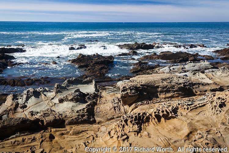 Earth, sky and sea meet at Bean Hollow State Beach where tafoni formations on the shore extend into the Pacific ocean and meet the horizon and cloud feathered sky.