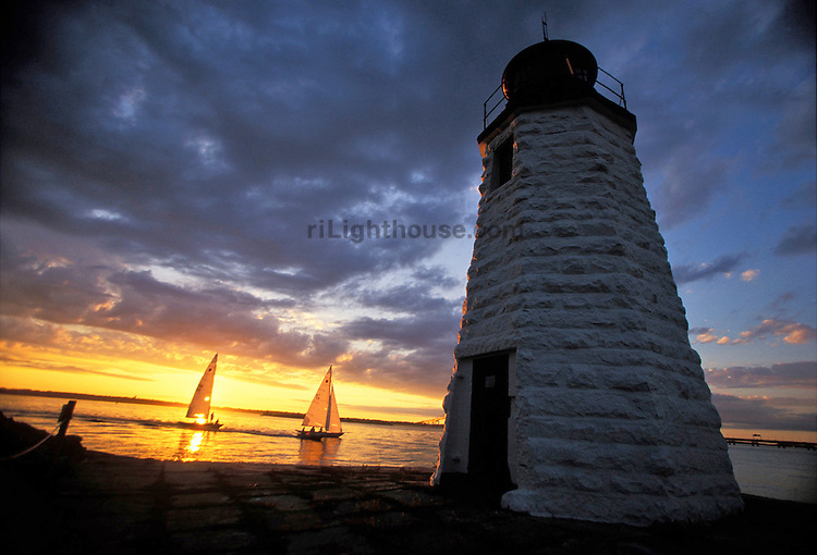 Sailors race back to port as the sun sets behind Goat Island Lighthouse.