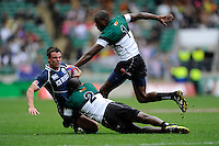 Lee Jones of Scotland is tackled by Daniel Hondo of Zinbabwe as Fortune Chipendu of Zimbabwe supports during the iRB Marriott London Sevens at Twickenham on Saturday 11th May 2013 (Photo by Rob Munro)