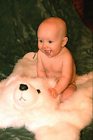 Baby boy smiling happily sitting on stuffed polar bear rug.  St Paul Minnesota USA