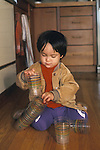 Berkeley CA Boy, one and a half-years-old using plastic glasses to experiment with stacking  MR