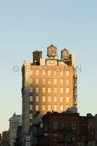 Iconic Water Towers atop a Classic 1912 Former Bank Building on Manhattan's Lower East Side, Jarmulowsky's Bank Building, 54 Canal Street at Orchard Street, New York City, New York State, USA<br /> <br /> One of the Lower East Side's classic buildings, the Jarmulowsky Bank Builidng was built by architects Rouse &amp; Goldstone in the &quot;Modern Renaissance Style.&quot;  It was completed in 1912 and was designated a New York City Landmark by the Landmarks Preservation Commission in 2009.<br /> <br /> The bank was established in 1873 by Sender Jarmulowsky, a Russian Jewish immigrant who went on to become one of the Lower East Side's most prominent businessmen....and was also a Talmudic scholar.   He was also one of the Lower East Side's most prominent philanthropists and served as the first president of the Eldridge Street Synagogue. <br /> <br /> Jarmulowsky's Bank was a well known institution among Yiddish speaking Jewish immigrants on the Lower East Side....and their relatives still living in Europe.  Immigrants here in New York City used the bank to send money to their relatives abroad....and to purchase steerage tickets (in Yiddish) so their relatives in Europe could also emigrate to the USA.  World War I broke out two years after this bulding was completed and the bank failed after a bank run as depositers withdrew funds to send to  relatives abroad.  The building was once the tallest building on Manhattan's Lower East Side.<br /> <br /> According to a Yiddish newspaper of the time, Sender Jarmulowsky was &quot; living proof that in America one can be a rich businessman but also a true, pious Jew.&quot;.