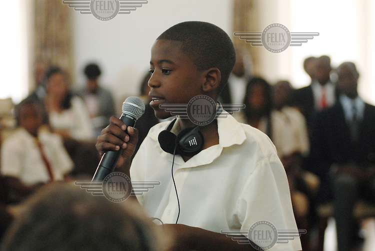 A pupil from Forces Primary School uses a microphone to make a speech at the presidential palace in Maputo, during talks involving international representatives to discuss education in the developing world.