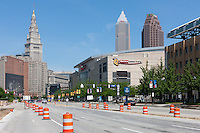 Construction barrels warn motorists of road improvements underway on Ontario Street in this view past Quicken Loans Arena toward Tower City and the Terminal Tower in Cleveland, Ohio.