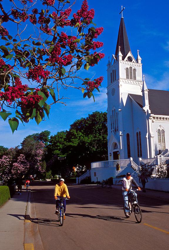 BICYCLE TRAFFIC PASS A CHURCH AND BLOOMING LILACS AT MACKINAC ISLAND, MICHIGAN.