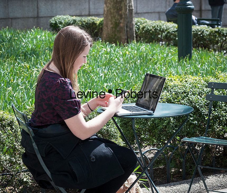 A woman with her phone and laptop in Bryant Park in New York City enjoys warm weather during her lunch hour on Thursday, April 3, 2014.  Temperatures are expected to rise into the mid 60's with plenty of sun today and Friday but clouds and a chance of showers arrive over the weekend.  (© Richard B. Levine)