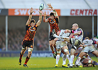 Brendon Leonard of the Ospreys box-kicks the ball as Jonny Hill and Alec Hepburn of Exeter Chiefs look to charge him down. European Rugby Champions Cup match, between Exeter Chiefs and the Ospreys on January 24, 2016 at Sandy Park in Exeter, England. Photo by: Patrick Khachfe / JMP