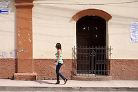 Young Honduran woman walking down a street in the Spanish colonial town of Gracias, Lempira, Honduras...