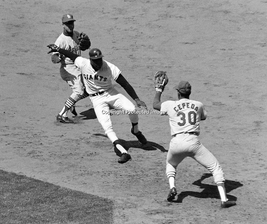 San Francisco Giants slugger Willlie McCovey is caught in a rundown between first and second base. St.Louis Cardinal 1st baseman Orlando Cepeda attempts tag..(1968 photo by Ron Riesterer)