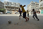 Boys play football in the Al-Shalti refugee camp in Gaza. Residents of the Palestinian territory are still reeling from the death and destruction of the 2014 war with Israel, and the continuing siege of the seaside territory by the Israeli military.