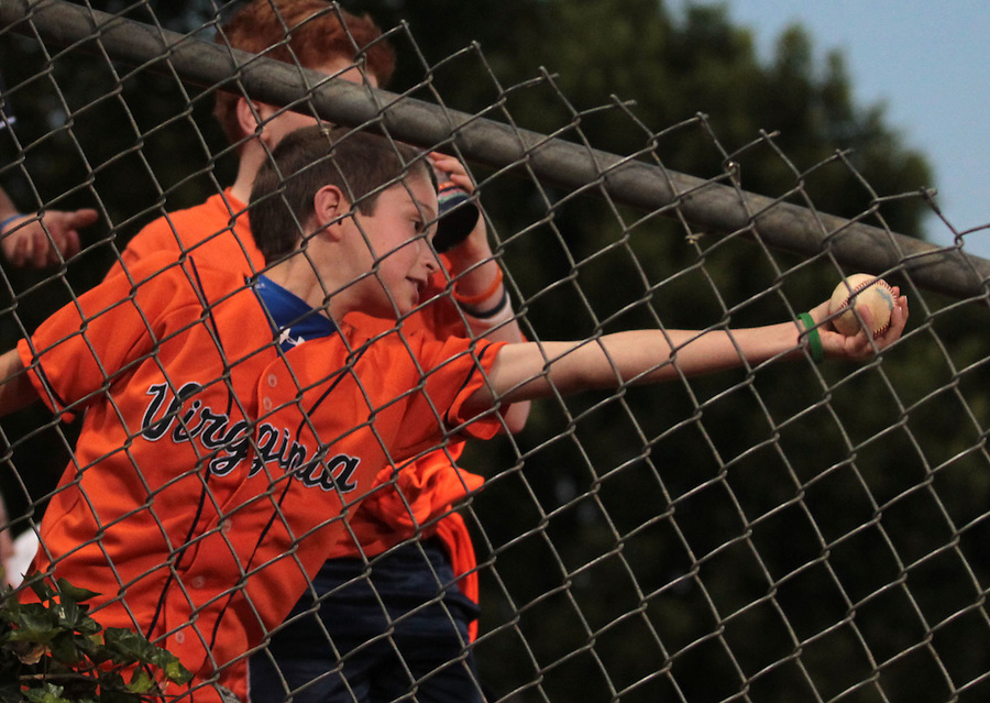 A young Virginia fan catches a ball thrown from the bullpen during the game against Arkansas Saturday night at Davenport Field in Charlottesville, VA. Photo/The Daily Progress/Andrew Shurtleff