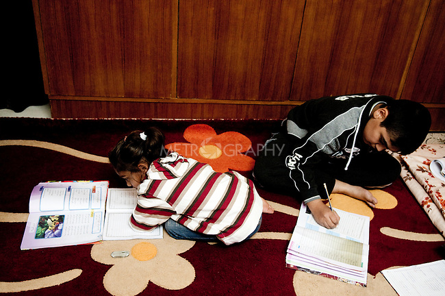KIRKUK, IRAQ: Ahmed Isam (14) studies at home with one of his sisters...Ahmed's father was shot and killed on November 18, 2006. Ahmed was wounded the following day at the funeral when an al-Qaeda suicide bomber detonated a bomb, killing 4 people and wounding 18. The day after, one of his sisters set her self on fire and killed herself due to grief...Ahmed's left side paralyzed and he has trouble speaking...Kirkuk, the oil-rich city in northern Iraq, is home to Kurds, Arabs, Turkomen, Christians, Kakayi, and numerous other ethnicities. Since 2003, thousands of its residents have been killed or injured in terrorist attacks...As the US military leaves Iraq, the future of this violent and ethnically diverse city remains unsure...Photo by Pazhar Mohammad/Metrography