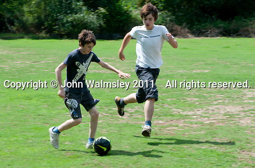 Football on the field, Summerhill School, Leiston, Suffolk. The school was founded by A.S.Neill in 1921 and is run on democratic lines with each person, adult or child, having an equal say.  You don't have to go to lessons if you don't want to but could play all day.  It gets above average GCSE exam results.